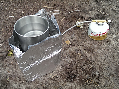 It might not be pretty, but the makeshift tin-foil wind-shield had a cup of water boiling in about four minutes.
